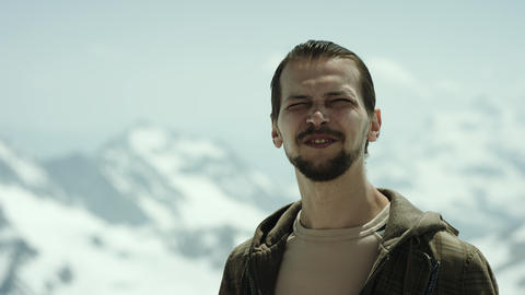 Young bearded man at mountain apex with scenic view squint eyes and talking Footage