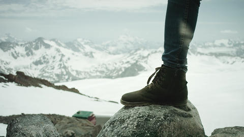 Traveler feet in leather boot stomps on rock at snowy mountain scenic view Footage
