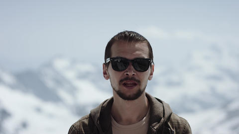Young bearded man at mountain top with scenic view turning around rapping Footage