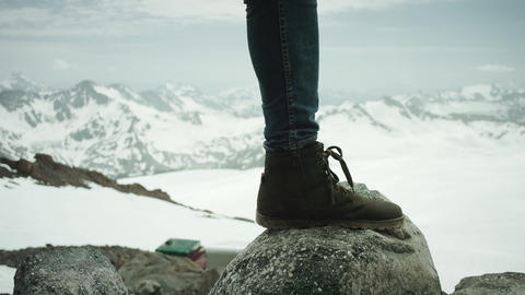 Traveler feet in leather shoe stomps on rock at snowy mountain scenic view Live Action
