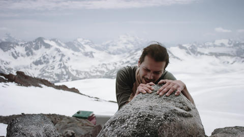 Young man climber climbs rock at snowy mountain scenic view on sunny day Footage