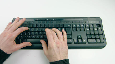 A man's hands typing on a keyboard on a white background Footage