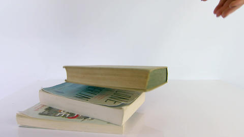 A pile of books being dropped on a white background Footage