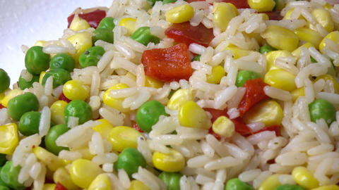 Heap of rice, corn, peas and red sweet pepper on the plate, 4K dolly shot Footage