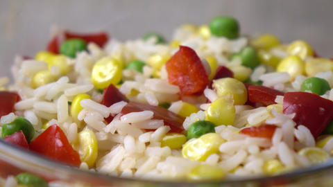 Bright mix of rice, corn, peas and red sweet pepper in glass bowl, 4K dolly shot Footage