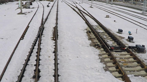 Low altitude motion aerial shot of several railway tracks and switches in snow Live Action