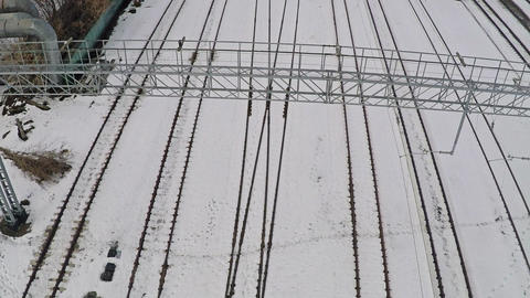 Multiple electrified railway tracks and switches in snow. Aerial view Archivo