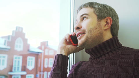 Cheerful young man with short beard speaking on his cellphone by the window Footage