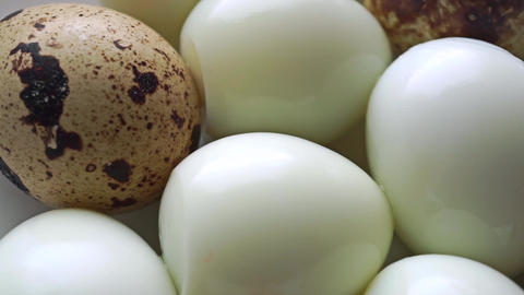 Dolly video of unshelled hard boiled and shelled quail eggs Footage