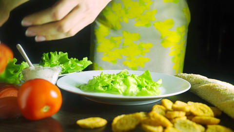 Girl with beautiful hands cooking Caesar chicken salad, close up video Footage
