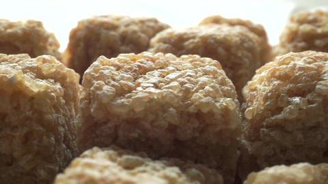 Brown sugar cubes close up dolly shot against white background Live Action