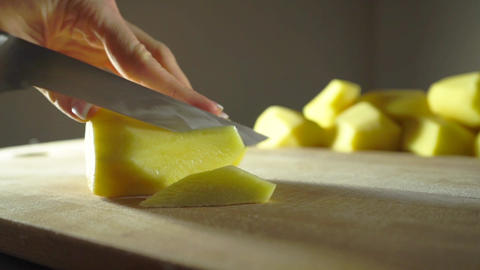 Young woman slicing peeled potato with a knife, slow motion shot Footage