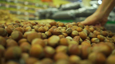 Picking some hazelnuts with a scoop in supermarket Footage