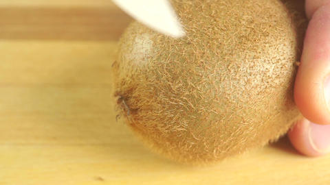 Cutting kiwi with white knife on wooden cutting board Footage