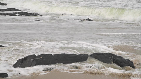 Waves on rocky and sandy beach. Slow motion video shot on cloudy day Footage