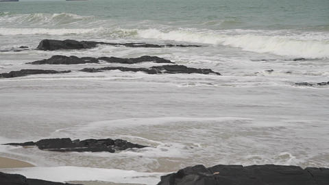 Sea surf on rocky and sandy beach. Slow motion video shot on cloudy day Footage