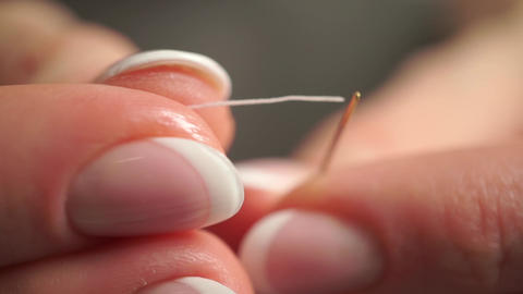 Threading a needle with a white thread. Extreme close up video Footage