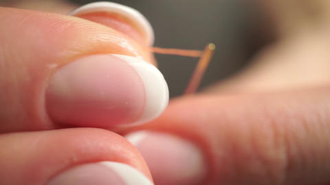 Threading a needle with an orange thread. Macro video Footage