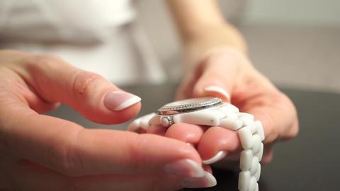 Woman with beautiful nail polish winding up her white wrist watch Footage