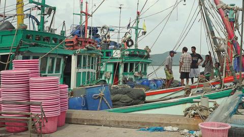 Thai fishermen on moored fishing boat Footage
