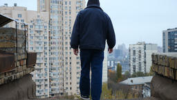 Young guy in a jacket jumping from the roof, suicide, death, city. 60 fps Footage