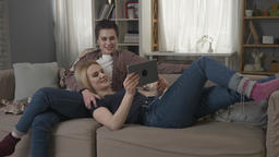 Lesbian couple is resting on the couch, and watching funny movie on tablet, a Footage