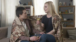 Two young, beautiful girls are sitting on the couch wrapping with warm plaid Footage