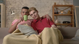 Two gay guys sit on the couch and watch TV, drink hot tea, use the remote Footage
