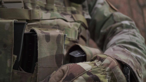 Soldier puts assault rifle ammo into pockets of his ammo vest. Close up shot Footage