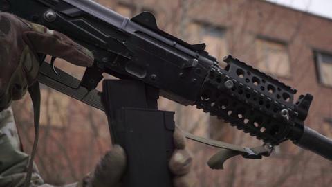 Changing a magazine of Kalashnikov assault rifle. Close up shot Live Action