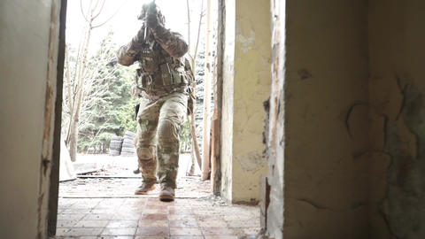 Unrecognizable armed soldiers enter ruined building Footage