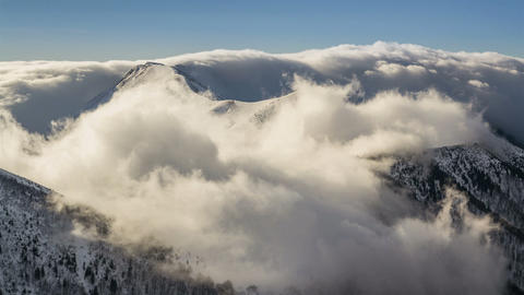 Winter snowy mountains with low clouds flying over ridge in morning light time Footage
