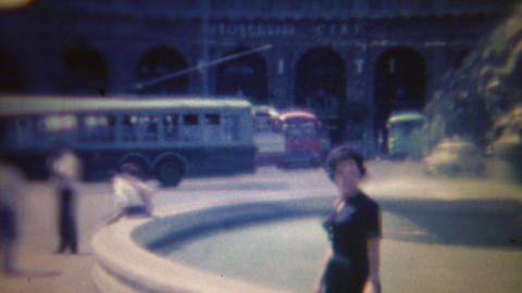 1963: Italian women strolls water fountain electric bus road travels Footage