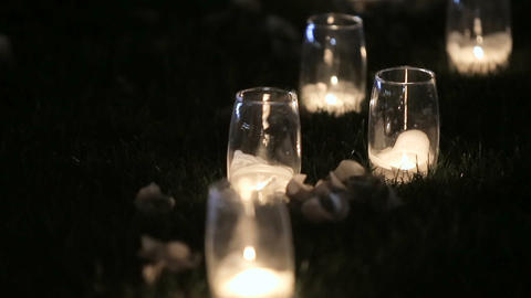Romantic burning white candles in glass vases standing on a grass for an evening Live Action