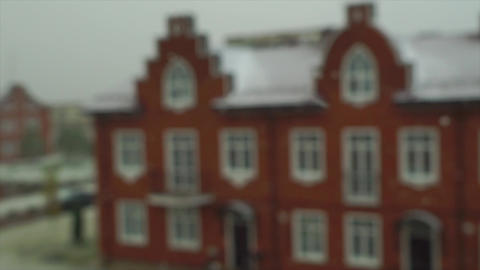 Slow motion video of snowflakes in front on red brick town house Footage