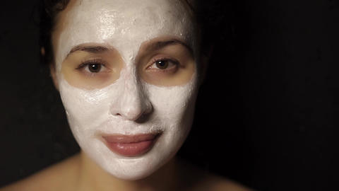 Beautiful young woman with a face pack on her face looking at the camera Footage