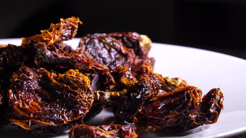 Rotating white plate with sundried tomatoes on black background Footage