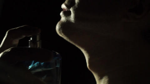 Young man sprays his perfume on his neck, slow motion video Footage