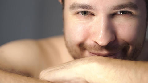 Young man with short beard and folded hands looking and smiling in the camera Footage
