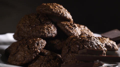 Rotating plate with homemade chocolate cookies on black background Footage