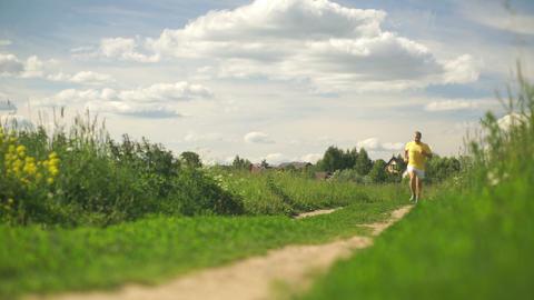 Man in a yellow t-shirt running across the summer field Footage