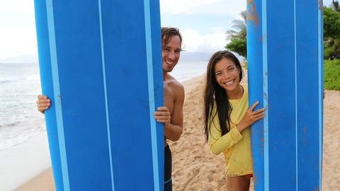 Surfing couple surfers posing with surfboard on beach on Hawaii Live Action