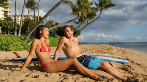 Couple surfing surfers talking having fun on Hawaii beach Maui Footage