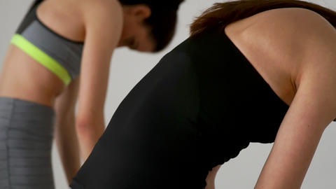 Close-up of 2 girls doing exercises from Pilates. Back view. Slowly tilt down Footage
