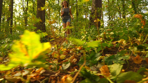 Beautiful girl running in sunny autumn forest, steadicam slowmotion shot Footage