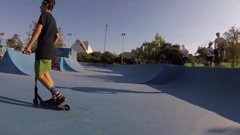 Boy Riding Kick Scooter Tailwhip Jump Flip Air Trick in Valencia Skatepark Bowl Footage