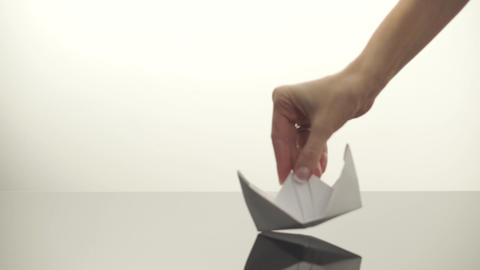 Paper boat slides on a reflective surface Footage
