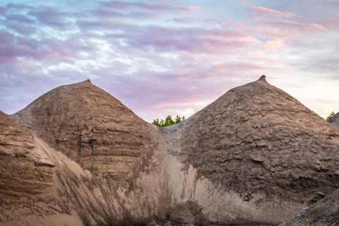 Two boobs formed from clay piles at pink sunset Photo