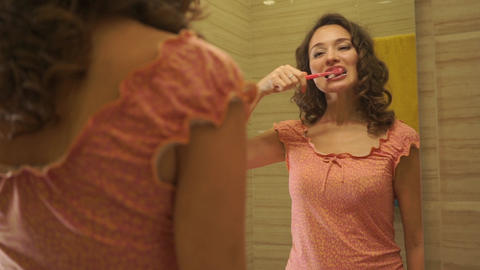 Beautiful girl in a pink dress brushes her teeth Footage