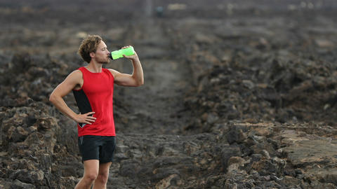 Man drinking water from bottle after fitness running workout outdoors Footage